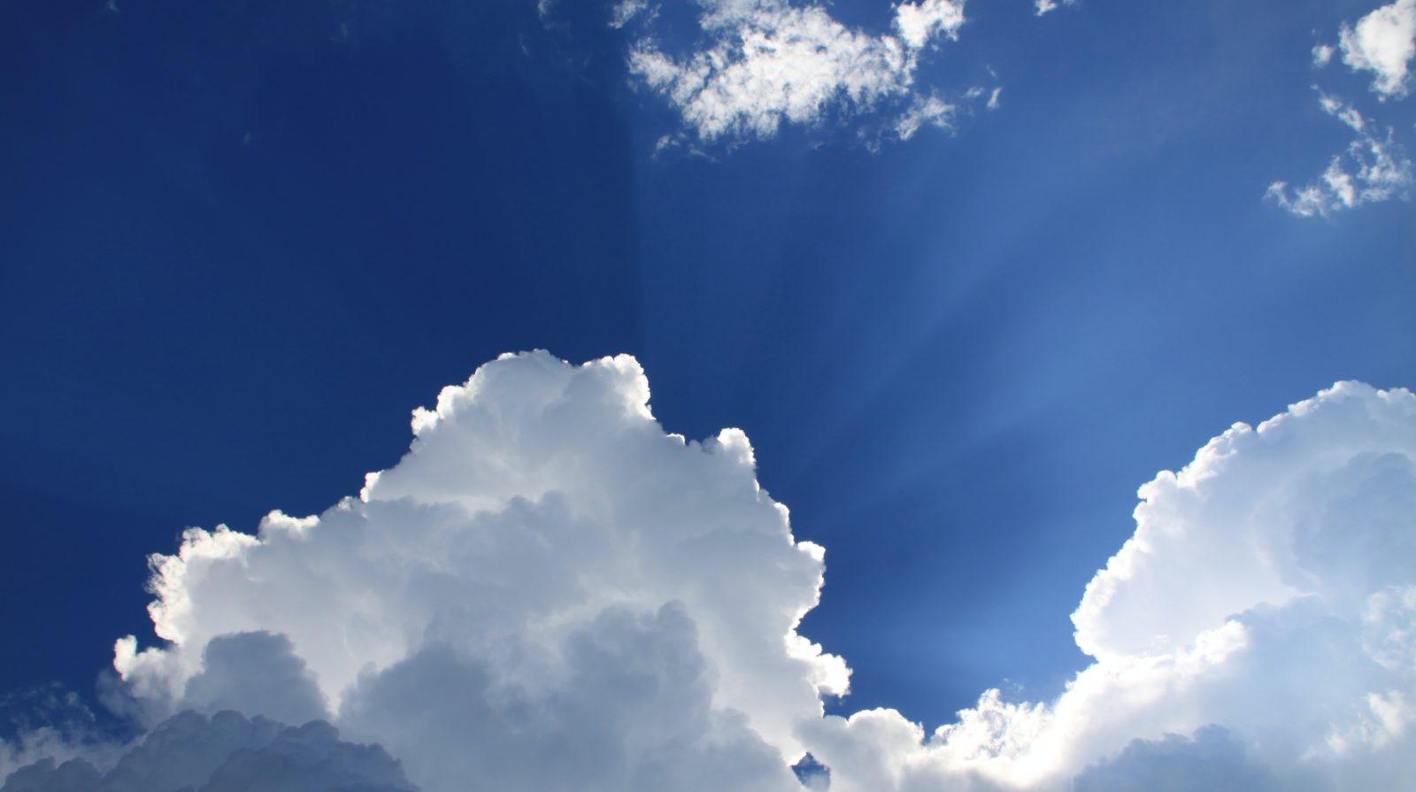 Blauer Himmel mit Wolken und Sonnenstrahlen